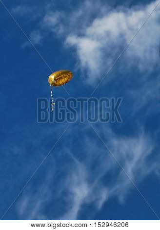Golden balloon escaping into a blue sky with fluffy clouds