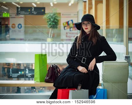 Beautiful girl in a hat with shopping bags in a shopping center. The concept of discounts, sales, shopping