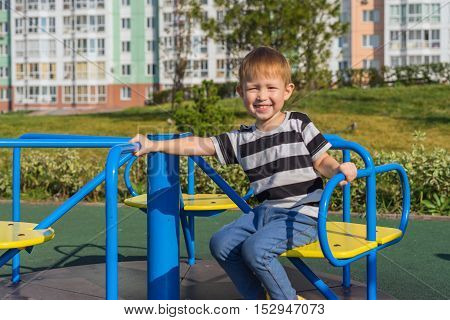 A boy rides a carousel at the playground in the city a warm sunny day.