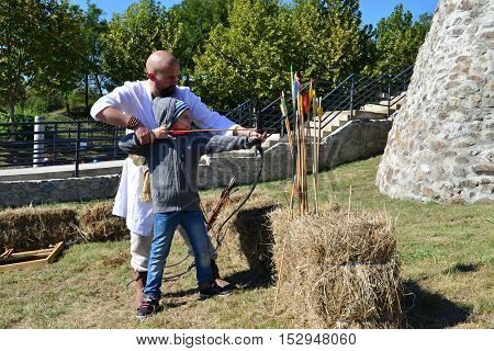DROBETA ROMANIA - 10.09.2016: medieval festival archer teacher training a kid with the bow