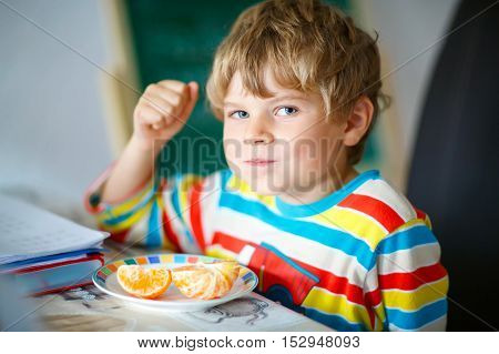 Adorable little kid boy in colorful clothes eating mandarin orange fruit. Happy smiling child. Healthy food, eating and lifestyle concept.