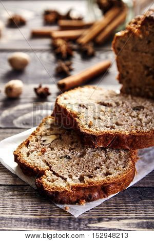 Delicious slices of homemade banana bread with nuts. Fragrant dessert for cup of tea on wooden table. Fresh bananas, cinnamon sticks, stars of anise and walnuts in the shell next to it. Banana loaf