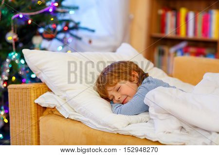 Little cute blond boy sleeping under Christmas tree and dreaming of Santa at home, indoors. Traditional Christian festival. Happy kid waiting for gifts.