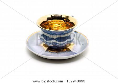 Empty small coffee cup on a saucer isolated on white background.