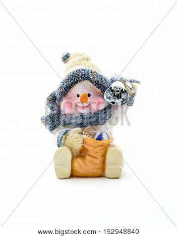 Figurine cheerful snowman holding a bell on a white background.
