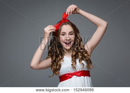 Beautiful teenage girl with long curly hair and red ribbon bow on head wearing white dress. Happy surprised expression. Studio portrait on grey background. Copy space.