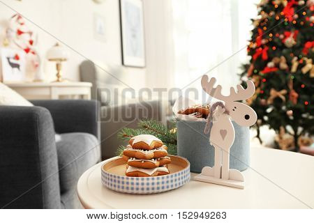 Tasty gingerbread cookies, Christmas decor and box on table against blurred background