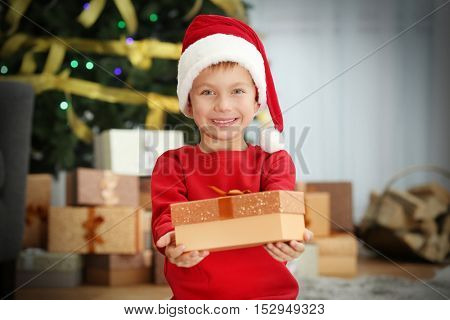 Cute little boy in Santa hat with Christmas present at home