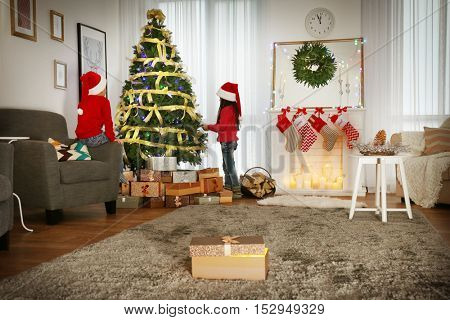 Cute little kids in Santa hats decorating Christmas tree at home