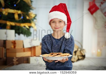 Cute little boy in Santa hat with plate of delicious cookies at home