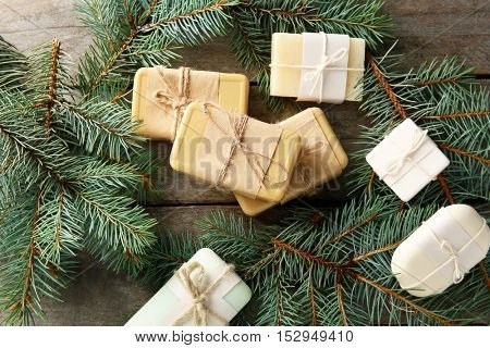 Pieces of coniferous soap and branches on wooden background