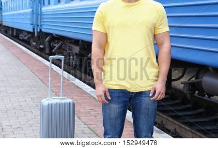 Young man in blank t-shirt standing on railway platform with suitcase, closeup