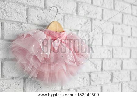 Cute pink skirt for girl hanging on white brick wall background
