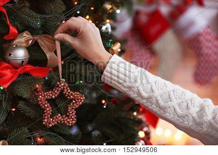 Female hand decorating Christmas tree, closeup