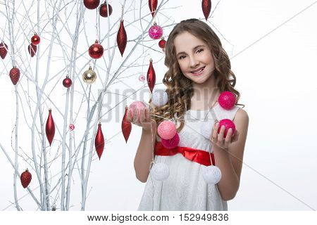 Beautiful teen girl with long curly hair in white dress with red ribbon belt standing near white tree branches wiht christmas decorations and holding pink garland. Studio shot on white background. Copy space.