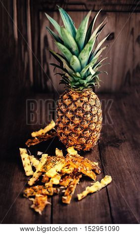 Ripe pineapples on wooden table with ananas stubs