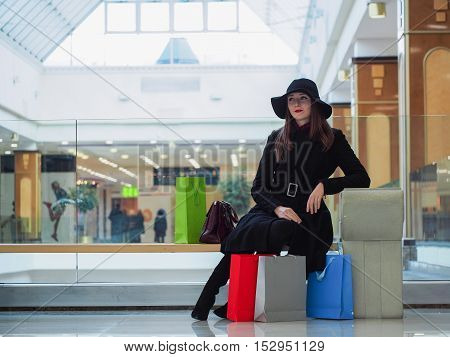 Beautiful girl in a hat with shopping bags in a shopping center.