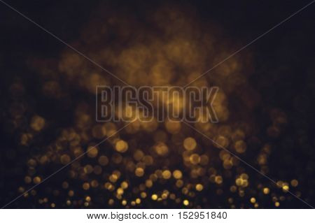 Dark Golden shining glitter background with sparkling lights. Defocused gold abstract festive shimmer