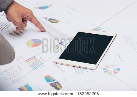 Businessman poiting at business report paper with tablet on the table.