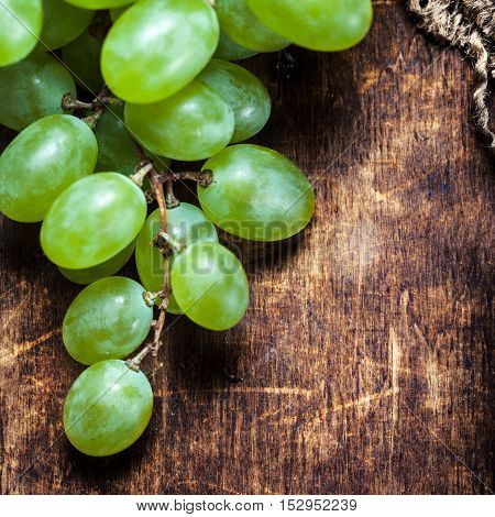 White grapes bunch over wooden background. Green grape country rustic style close up with copy space