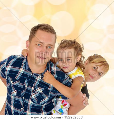 Portrait of happy family of three. Happy mother and daughter peeking from behind dad. close-up.Brown festive, Christmas background with white snowflakes, circles.