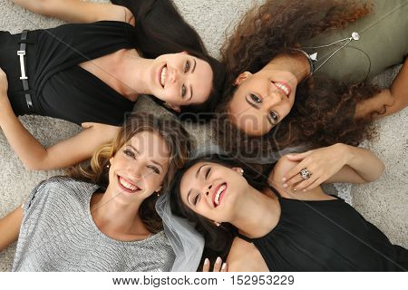 Beautiful girls lying on floor, top view