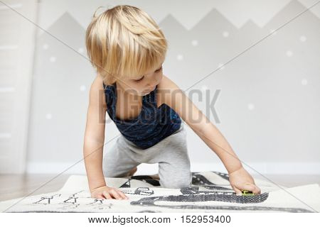 Indoor Shot Of Adorable Caucasian Two-year Old Baby Boy With Fair Hair Holding Toy Car While Playing