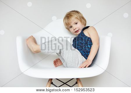 Portrait Of Adorable Barefooted Child With Blond Hair Dressed In Gray Pants And Sleeveless Shirt Enj