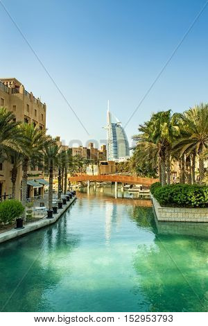 DUBAI, UAE - OCTOBER 06, 2016: The Iconic Burj al Arab seven star hotel in Dubai taken set against azure waters of the artificial lake in Madinat Jumeirah surrounded by palm trees
