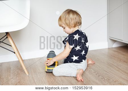 Cute Baby Boy With Blonde Hair Sitting On Wooden Floor In His Bedroom, Holding His Favourite Toy And