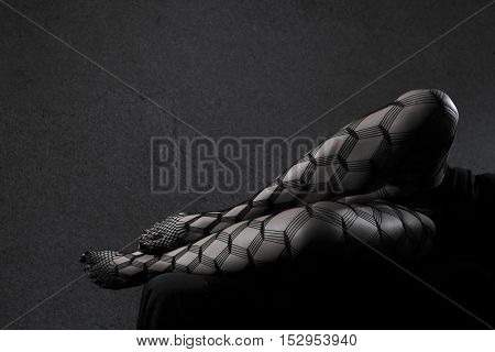 Low key grey scale photo of sexy female nude legs in net tights against dark background with copy space horizontal view