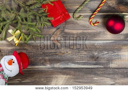 Fir tree branches with gift box cane candies christmas ball and funny snowman on wooden background with copy space.