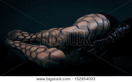 Low key special toned photo of sexy female nude legs in net tights and hands in black leather gloves against dark background horizontal view