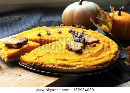 American pie with pumpkin and mascarpone on the table with fresh pumpkin and maple leaves