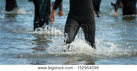 Triathletes group,splash of water while triathletes running in sea