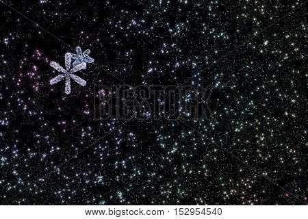 Beautiful winter abstract background with snowflakes and stars closeup on a black background