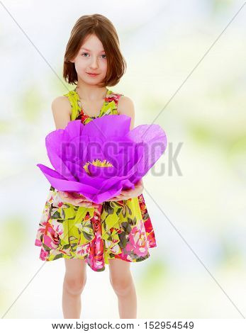 Adorable little girl in summer dress holding a large purple flower made of paper.Summer white green blurred background.