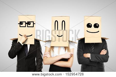 Businessmen and woman with smiling box on head
