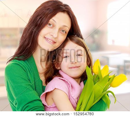 Happy mother gives her daughter a bouquet of yellow tulips.During a lesson in school.