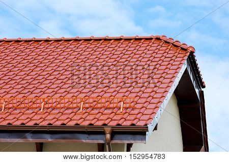 Modern roof of the red glazed ceramic tile and snow guards