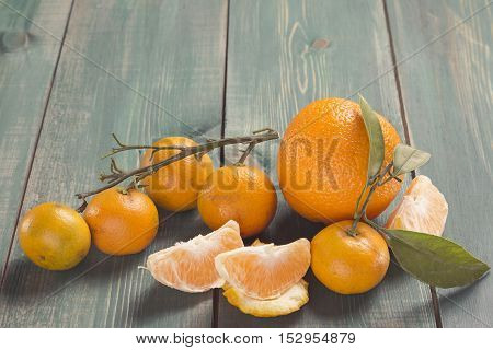 Tangerines with branch leafs and orange slices on green wooden table.