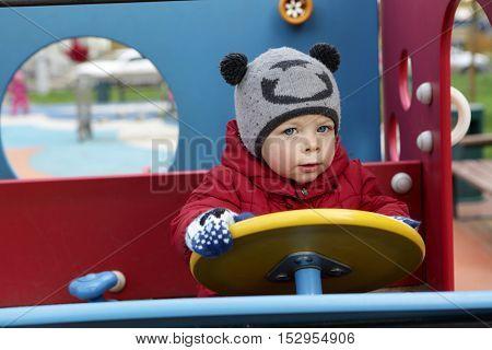 Child driving toy car at autdoor playground