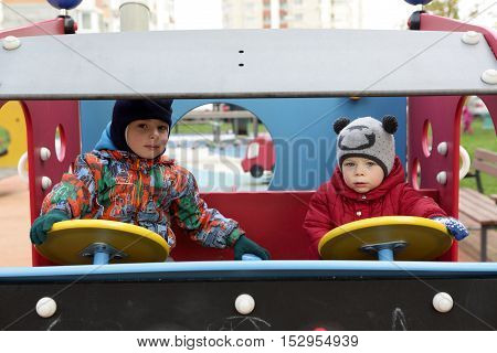 Two brothers driving toy car at autdoor playground