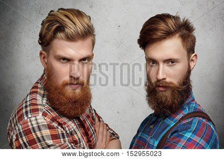 Two Handsome Young Unshaved Men With Hipster Beards Dressed In Stylish Checkered Shirts, Standing Wi