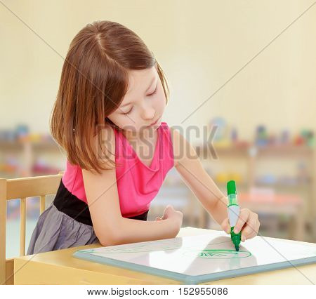 Little girl schoolgirl sits and draws at the table, green marker on the white Board. In the children's room where there are shelves with toys.