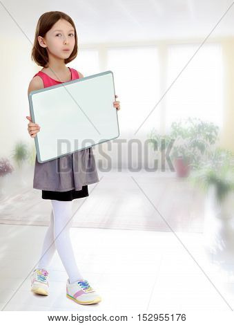Beautiful, small, slender girl, holding in front of a white poster.In the room with the big bright window in the wall.