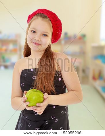 Cute little girl in fancy dress, holding a green Apple. Close-up.In the children's room with toys