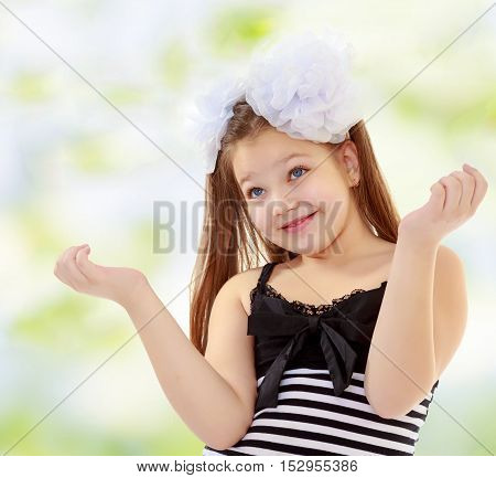 Beautiful, chubby, long-haired little girl with big white bows on the head . girl gesturing with his hands. Close-up.Summer green and white background.