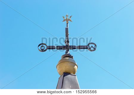 Old weathervane against a blue sky, east and west