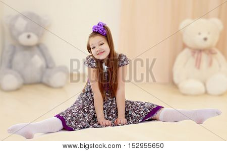 Caucasian little girl with a big purple bow on her head. Girl shows how to do the splits.In the nursery with Teddy bears.